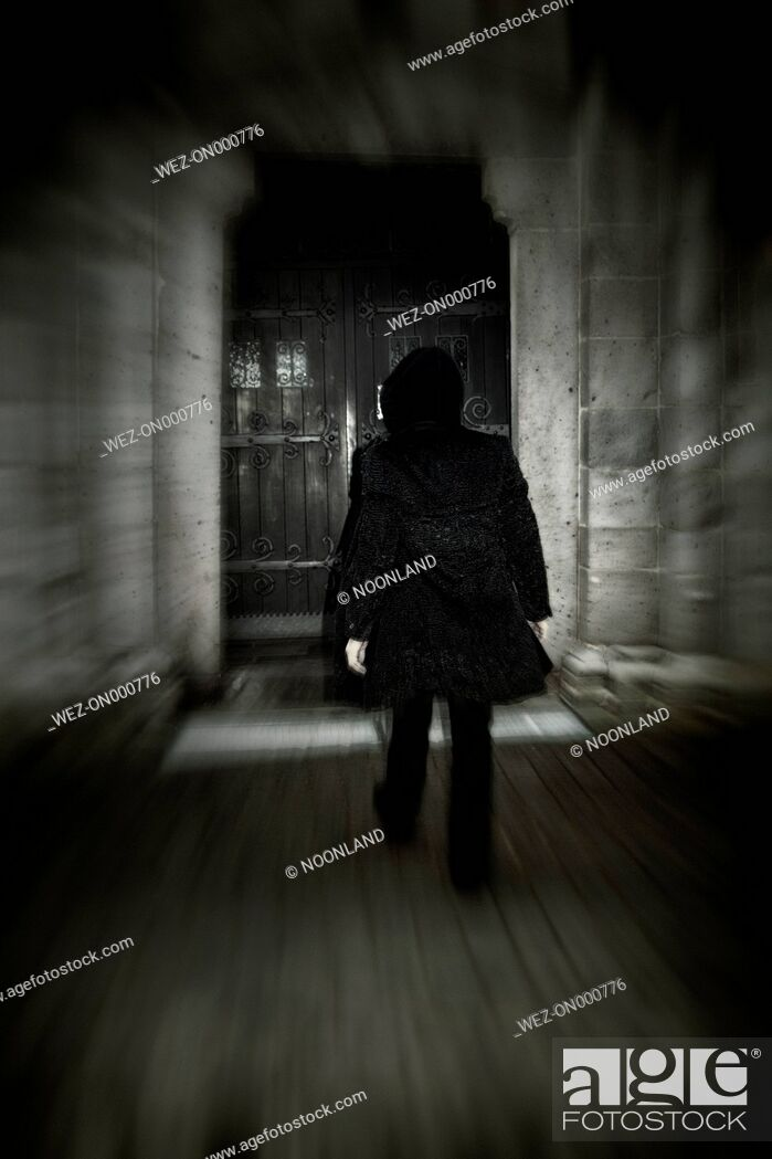 Stock Photo: Man with hooded jacket walking towards old door.
