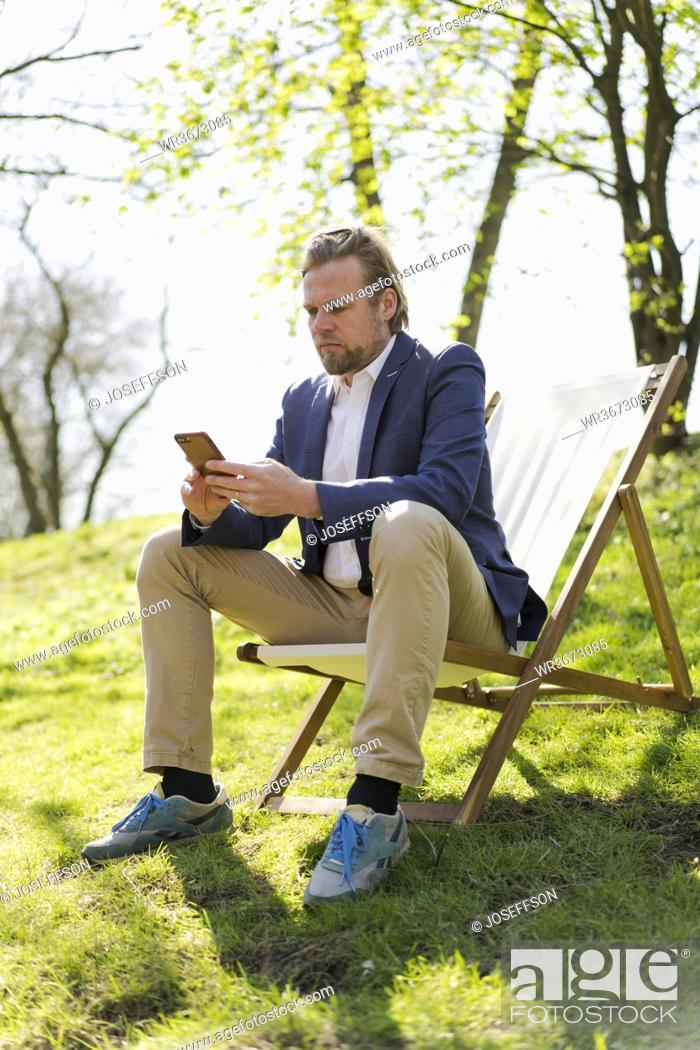 Stock Photo: Mature businessman text messaging through mobile phone while sitting on chair at park.