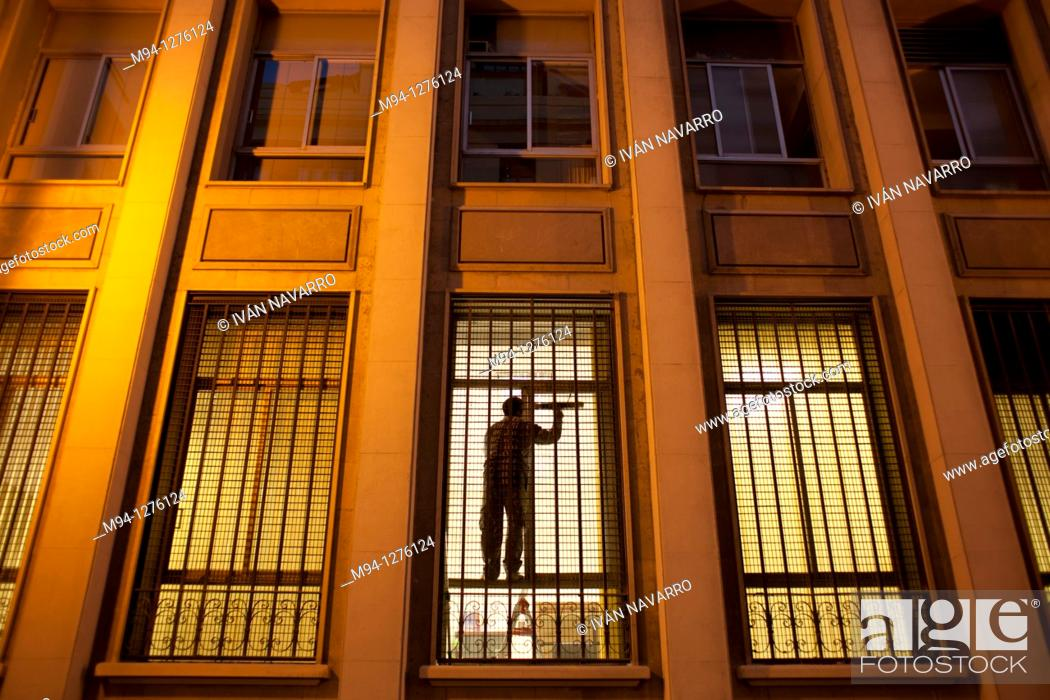 Stock Photo: man cleaning a window.