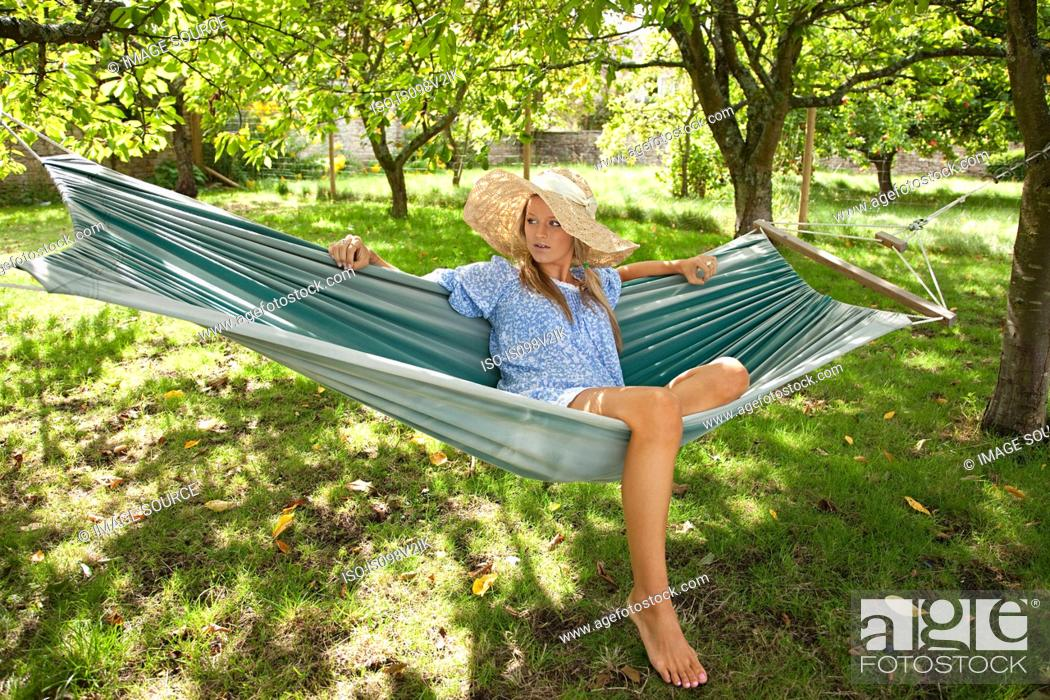 Stock Photo: Young woman relaxing in hammock.