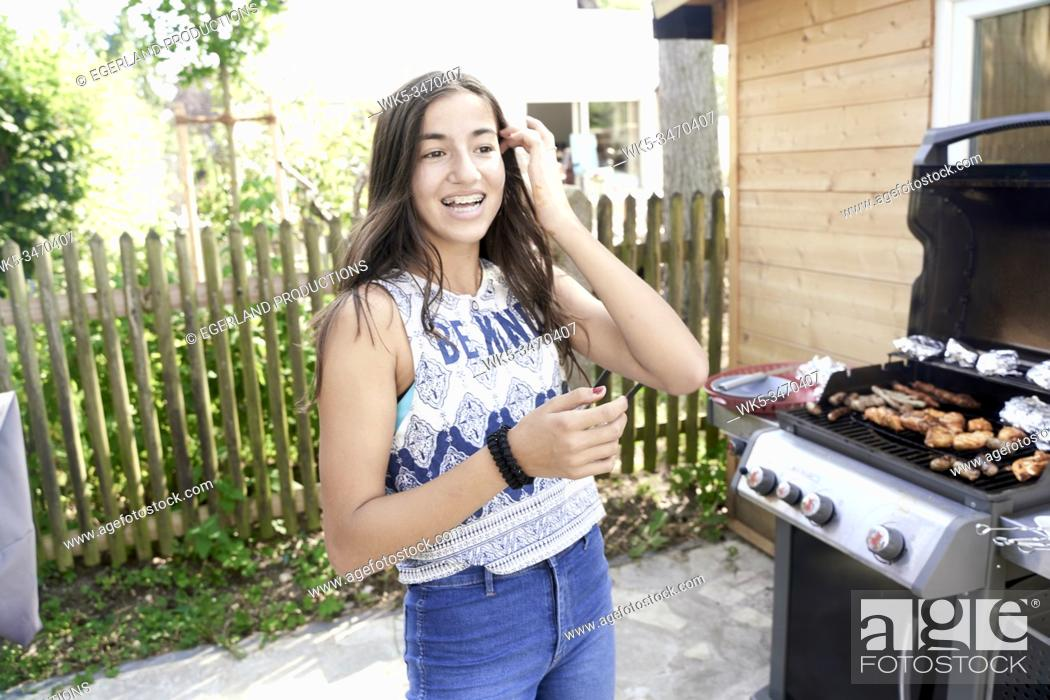 Stock Photo: Young girl cooking on barbecue.