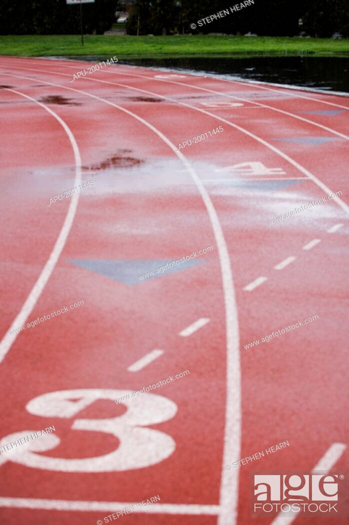 Stock Photo: Athletic track lanes at stadium wet with reflection.