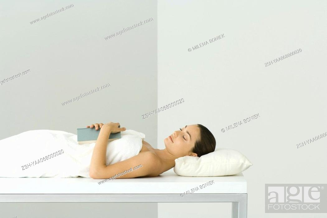 Stock Photo: Woman lying on massage table, holding book on chest, eyes closed.
