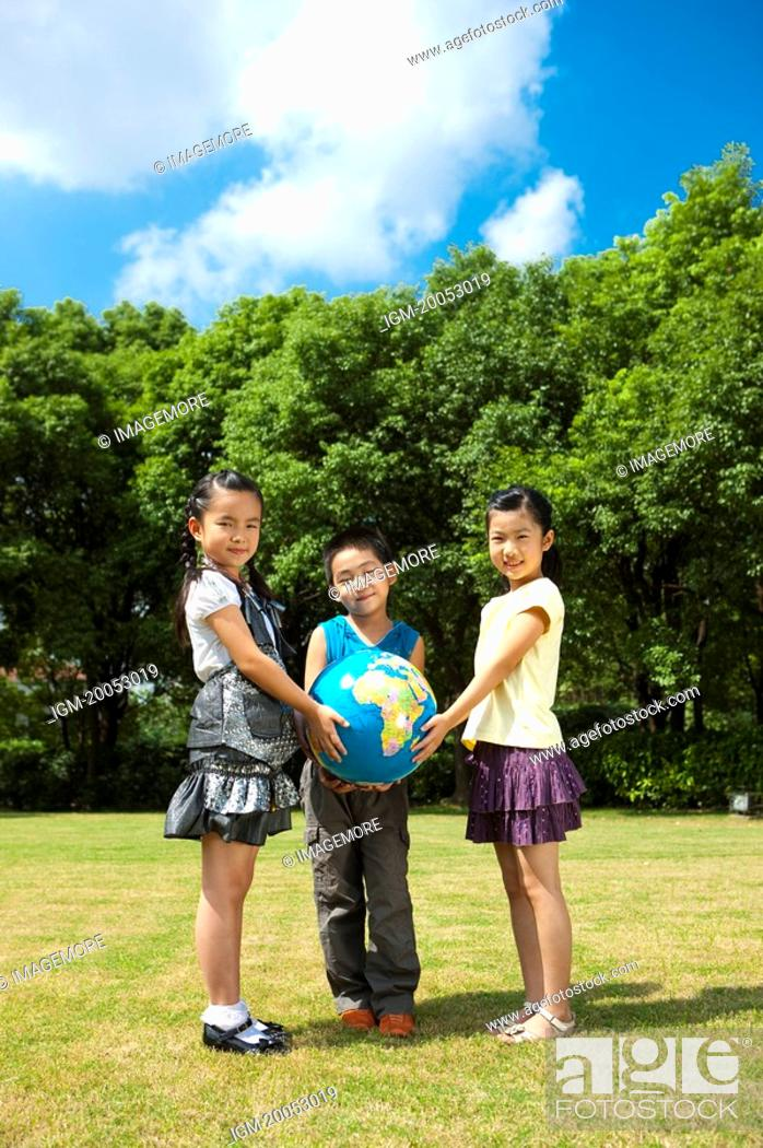 Stock Photo: Three children standing on the lawn and holding the globe together.