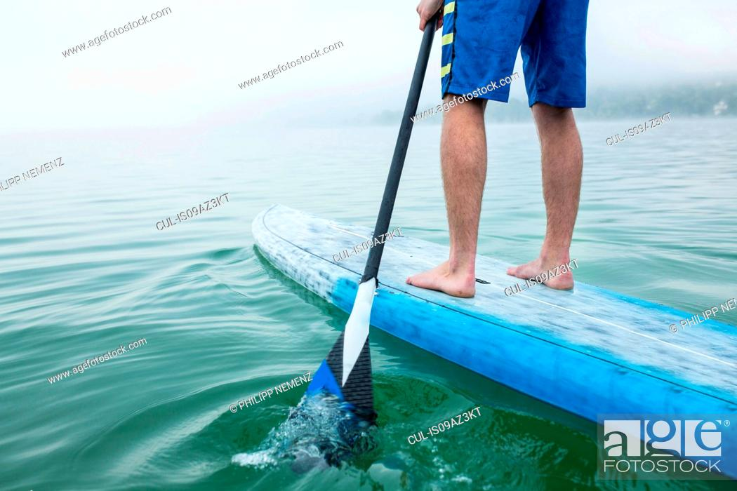 Stock Photo: Legs of young man stand up paddleboarding on lake Pilsensee, Germany.