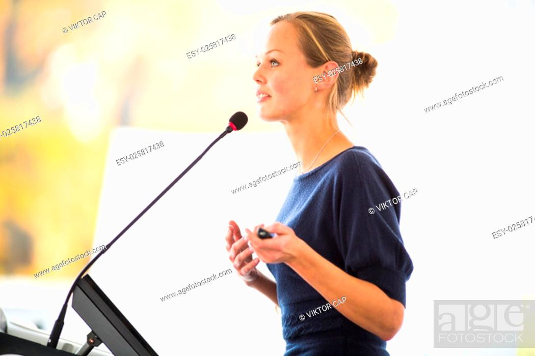 Stock Photo: Pretty, young business woman giving a presentation in a conference/meeting setting (shallow DOF; color toned image).