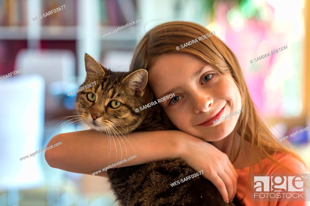 Stock Photo: Portrait of smiling girl with her tabby cat.