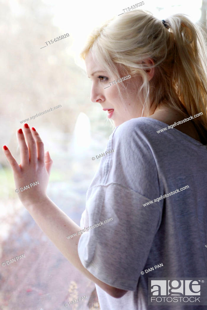 Stock Photo: Young woman looking out of window, sad, depressed, anticipating something, boredom.