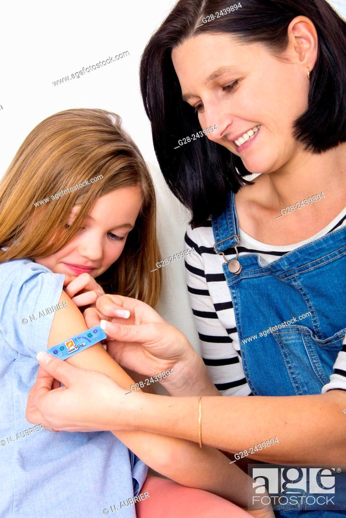 Stock Photo: Mother putting a clean dressing on the arm of her daughter.