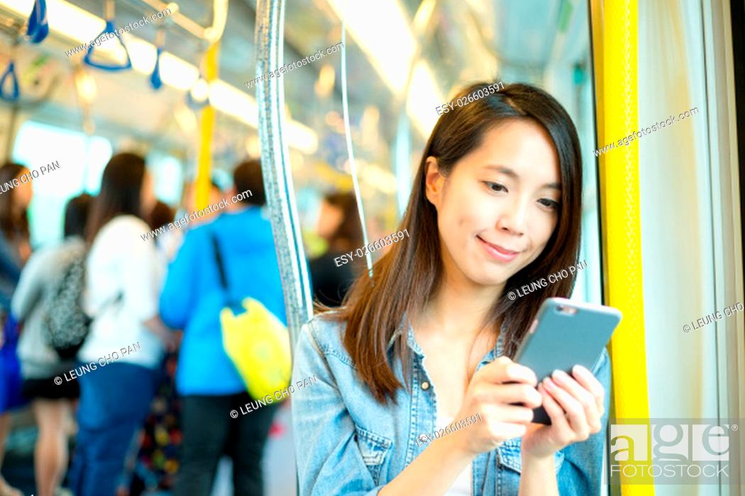 Stock Photo: Woman use of mobile phone inside train compartment at Hong Kong.