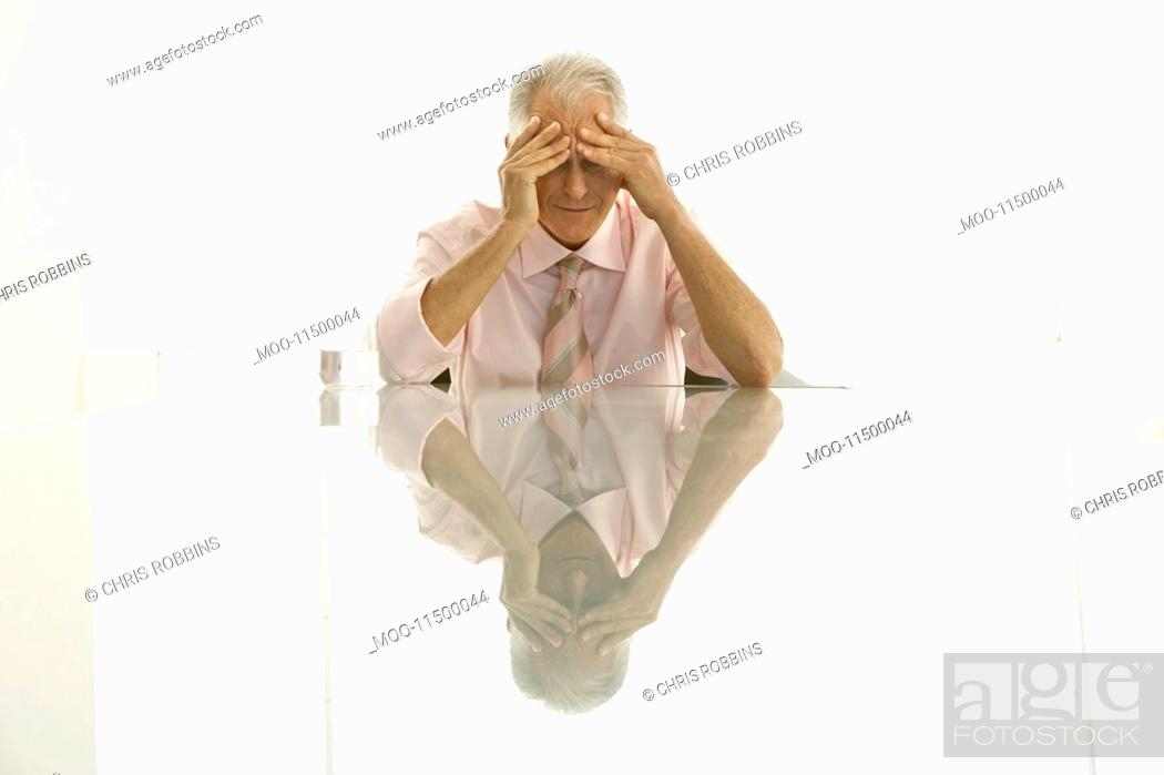 Stock Photo: Stressed businessman sitting at table.