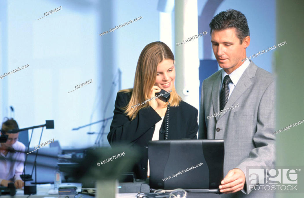 Stock Photo: Two businesspeople in front of laptop, businesswoman talking on phone.