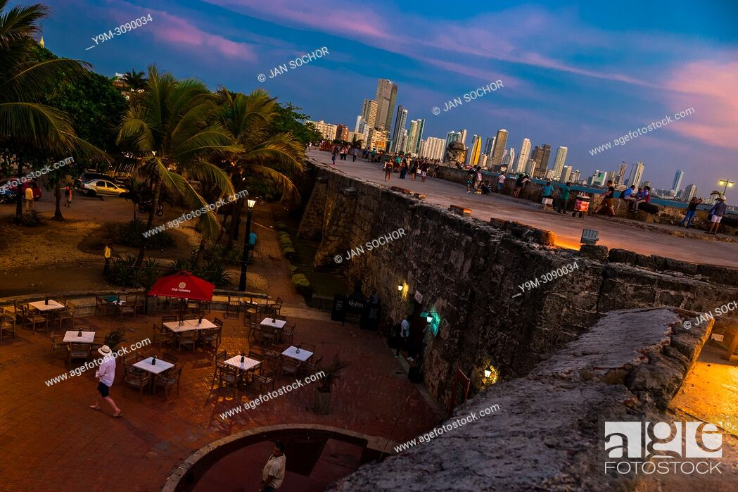 Stock Photo: Tourists walk on and along the stone walls, surrounding the colonial walled city, at twilight in Cartagena, Colombia, 14 April 2018.