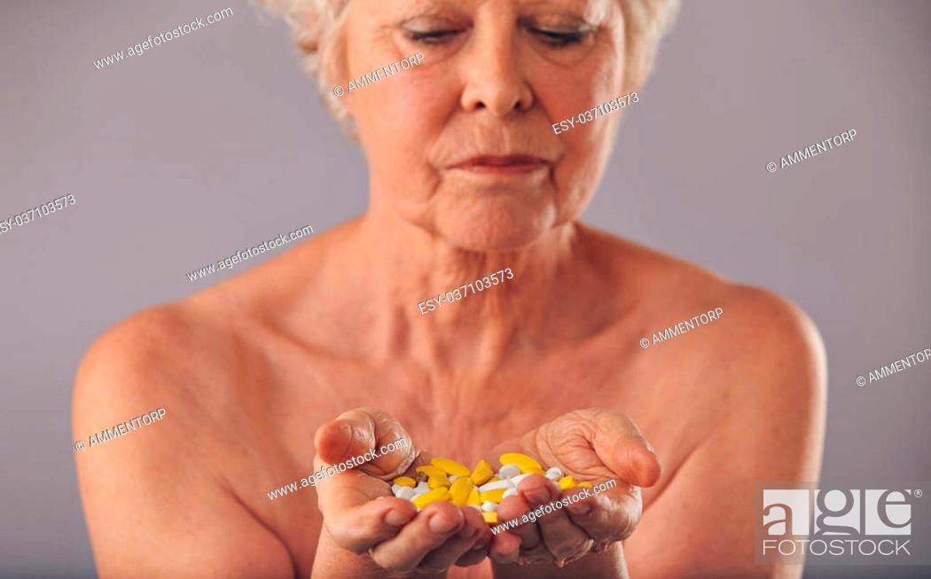 Stock Photo: Closeup image of a mature woman holding pills in her hand against grey background. Medication for long life.
