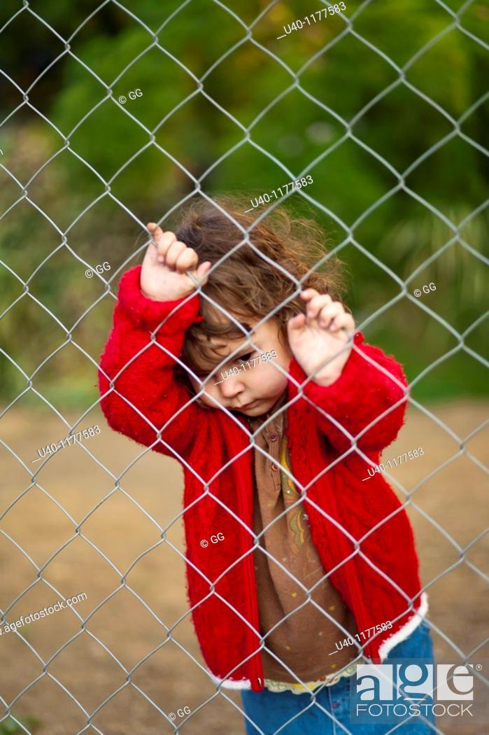Stock Photo: Young girl behind fence.