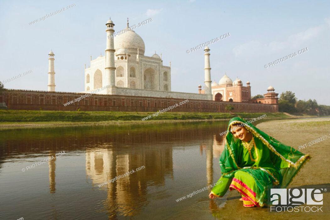 Stock Photo: Young woman crouching on the riverbank, Taj Mahal, Agra, Uttar Pradesh, India.