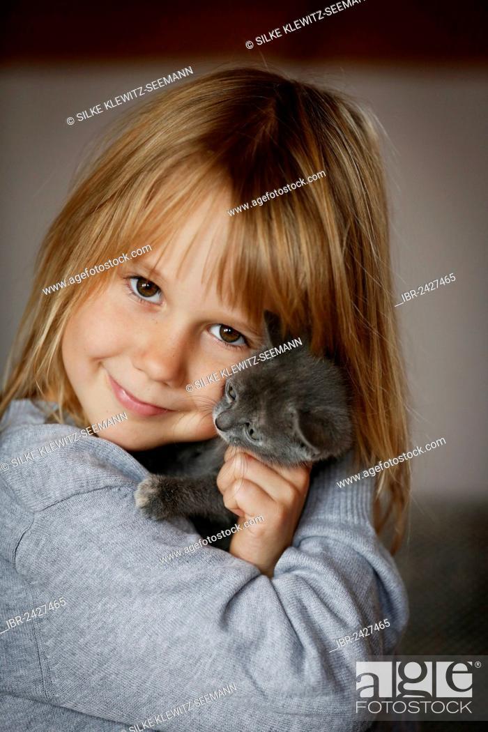 Stock Photo: Girl, 7 years, cuddling a kitten, portrait.