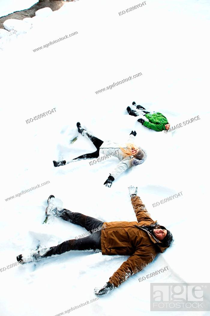 Stock Photo: Family making snow angels.