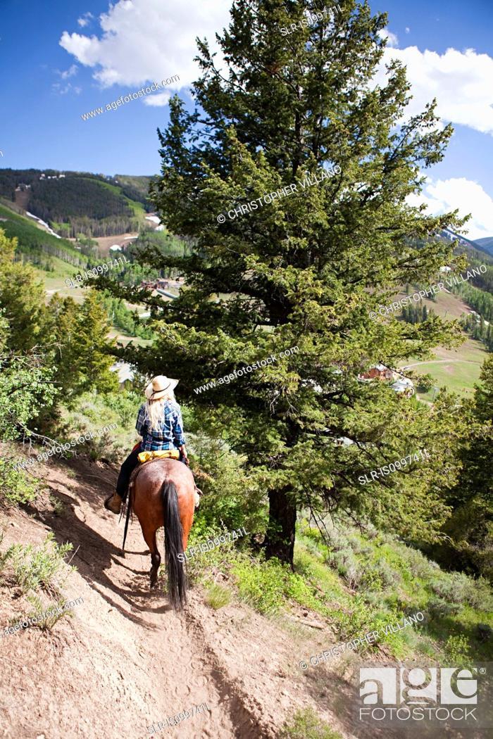 Stock Photo: Woman horse riding through Beaver Creek, Colorado, USA.