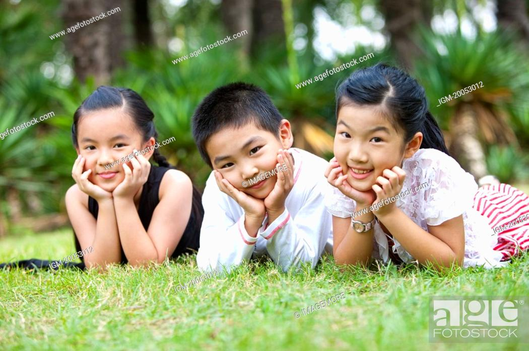 Stock Photo: Three children lying on grass with hands on chins, looking at the camera together.
