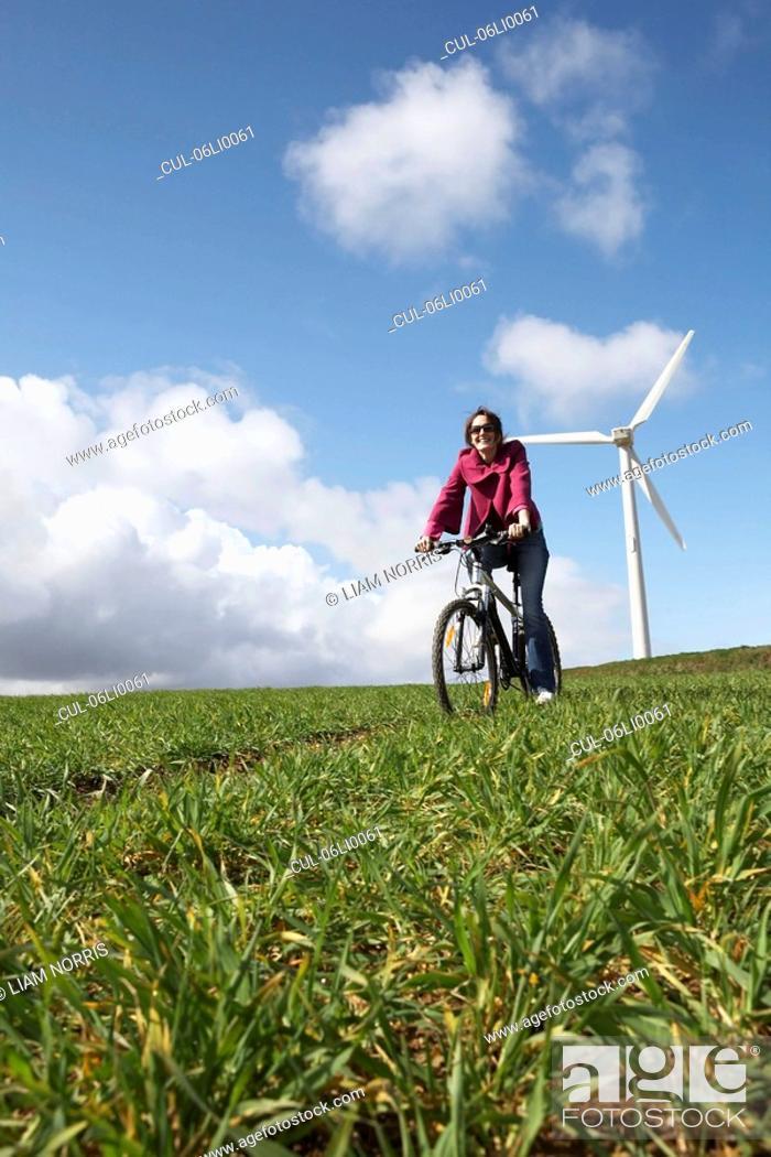Stock Photo: Woman riding a bike on a wind farm.