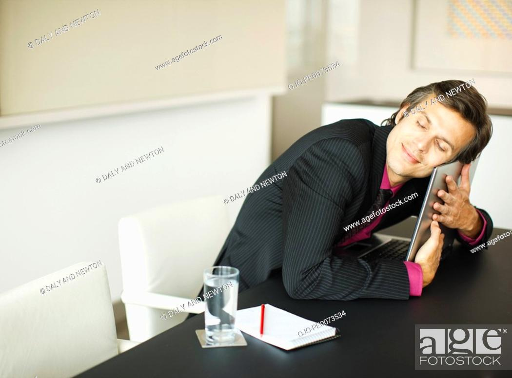 Stock Photo: Smiling businessman hugging laptop in conference room.