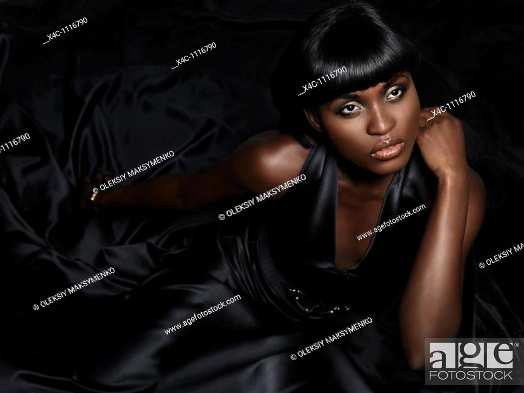 Stock Photo: Beautiful young woman wearing long black dress looking up at the light  High fashion photo.