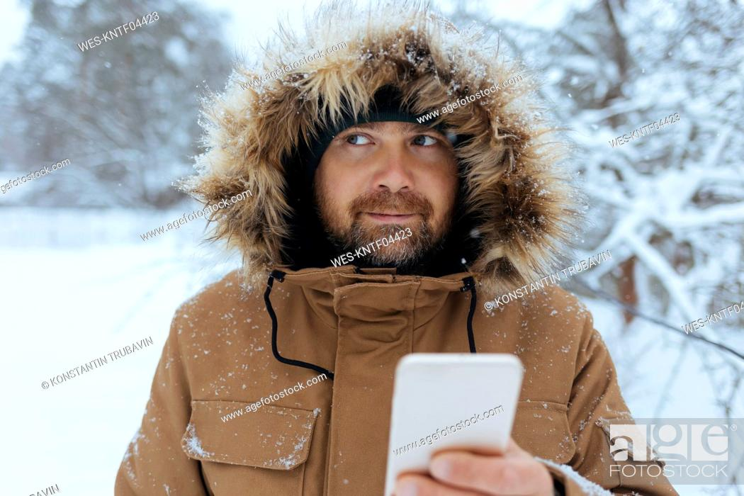 Photo de stock: Portrait of pensive man with cell phone in winter.
