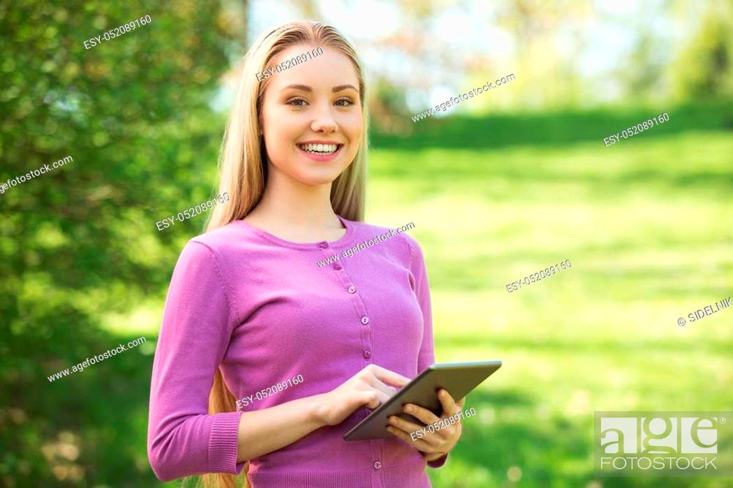 Stock Photo: Nice looking young woman outdoors. Woman using tablet computer and looking at camera. Beautiful green park as a background.
