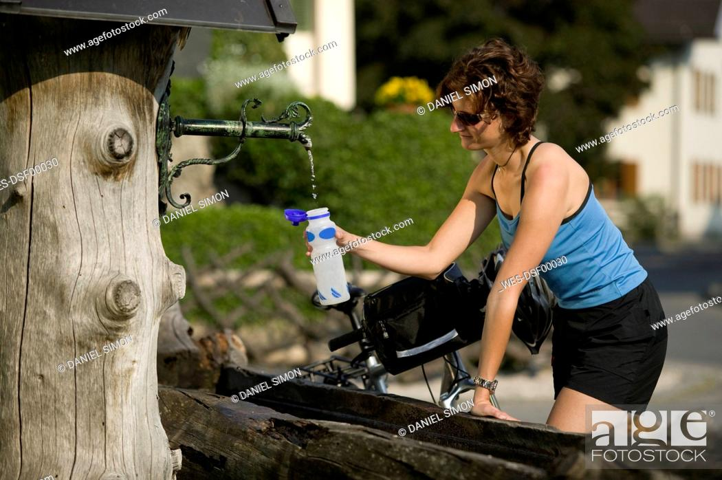 Stock Photo: Germany, Bavaria, Seeshaupt, Woman filling water bottle.