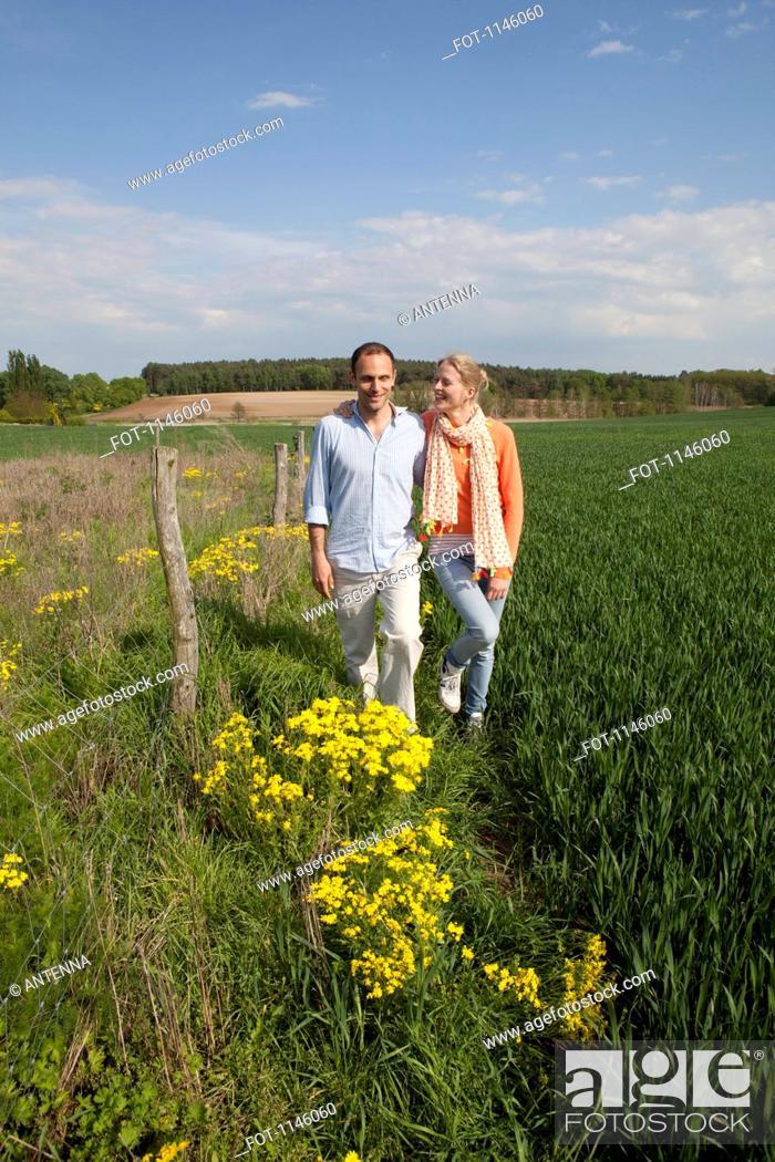 Stock Photo: A couple walking side by side in a field.