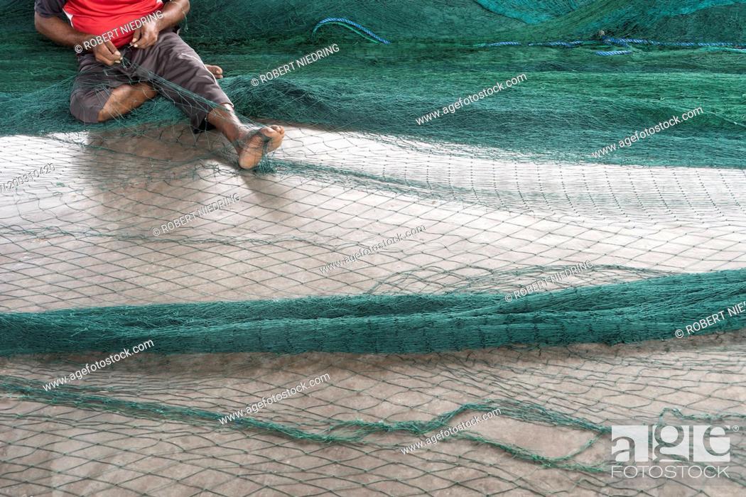 Stock Photo: Fisherman repairing fishing net, Western Province, Sri Lanka.