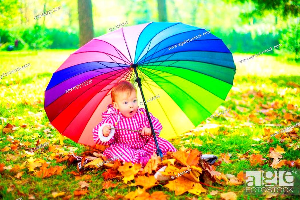Stock Photo: happy baby girl with a big umbrella in the autumn park.