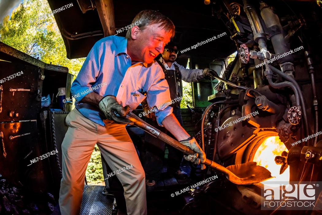 Stock Photo: Governor John Hickenlooper (of Colorado) acts as the train fireman adding coal, stoking the boiler on the steam locomotive on a visit aboard the the Cumbres &.