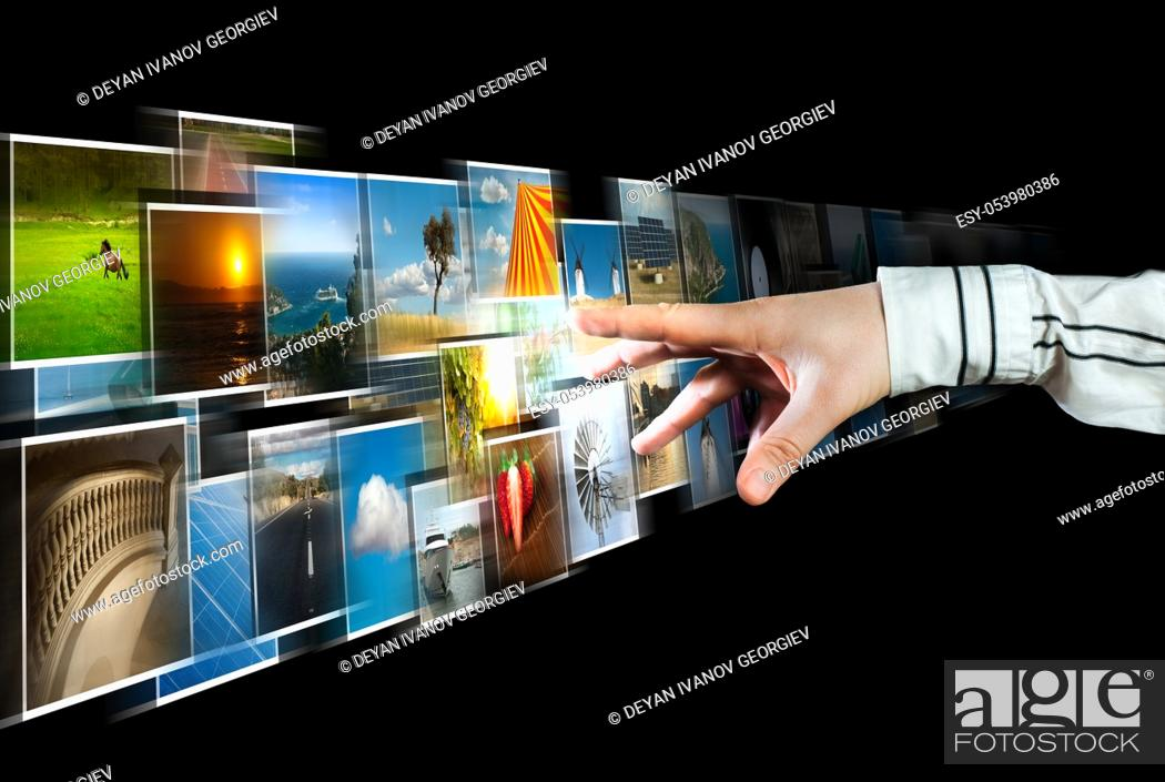 Stock Photo: Hand reaching images streaming from the deep on black background.