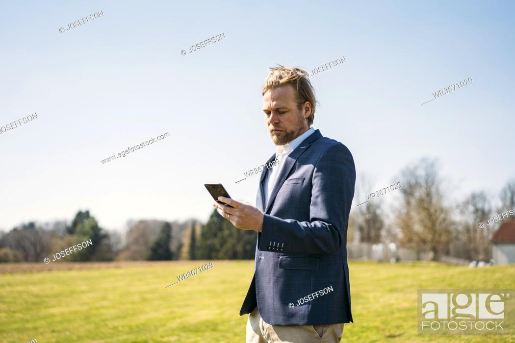 Stock Photo: Businessman using smart phone while standing at park against clear sky on sunny day.