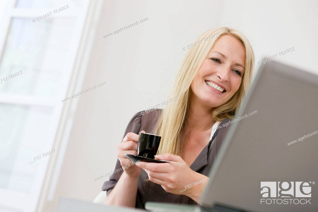 Stock Photo: Woman working on laptop at home.