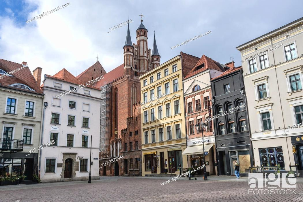 Stock Photo: Town houses on main square of Old Town in Torun, Kuyavian Pomeranian Voivodeship of Poland, view with Church of Assumption of Blessed Virgin Mary.