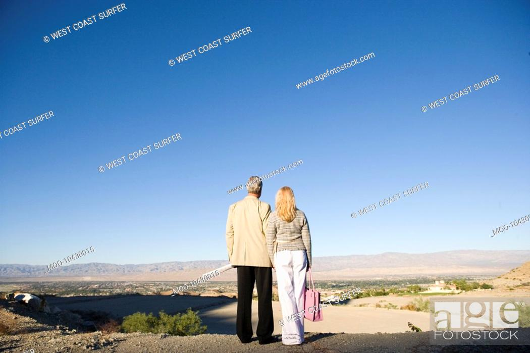 Stock Photo: Couple looking at plot for new home back view.