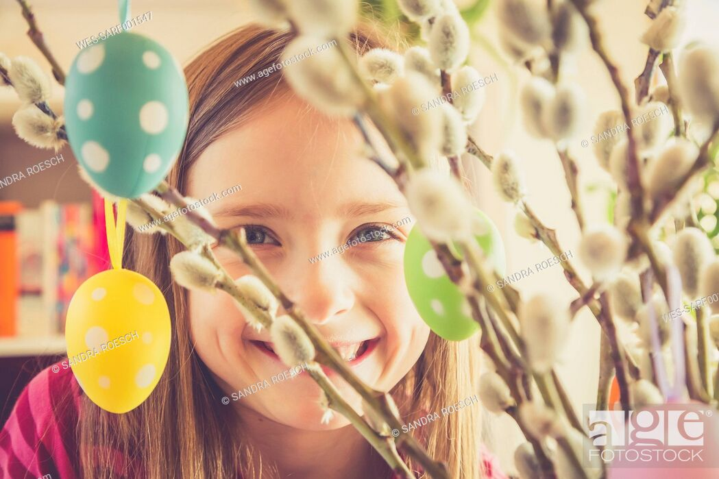 Stock Photo: Portrait of smiling girl behind Easter bouquet.