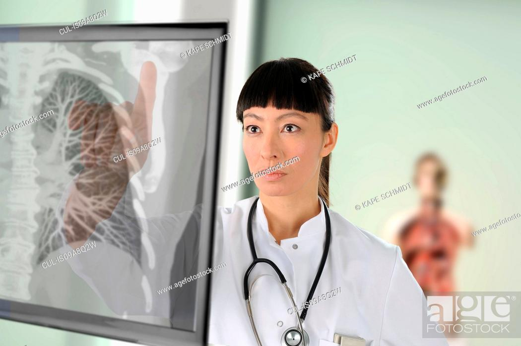 Stock Photo: Doctor looking at chest image on screen.