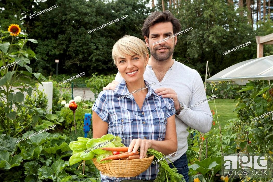 Stock Photo: Germany, Bavaria, Nuremberg, Mature couple with vegetables in garden.