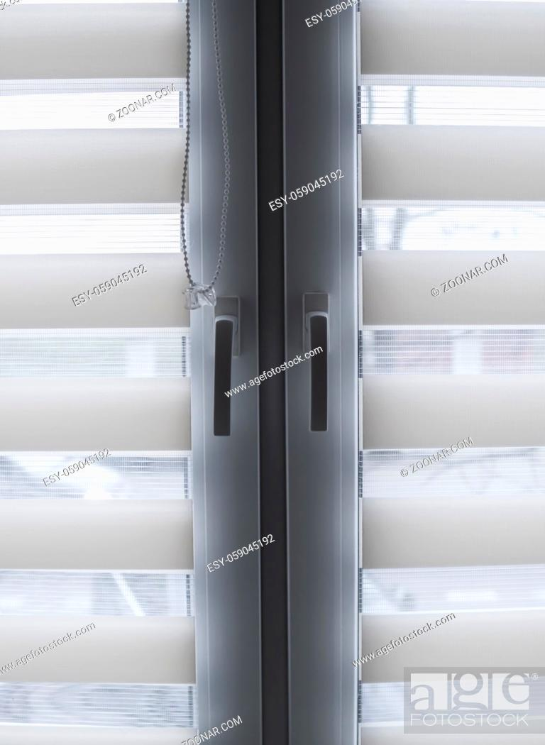 Stock Photo: White fabric roller blinds on the white plastic window in the living room. Roll curtains indoor.