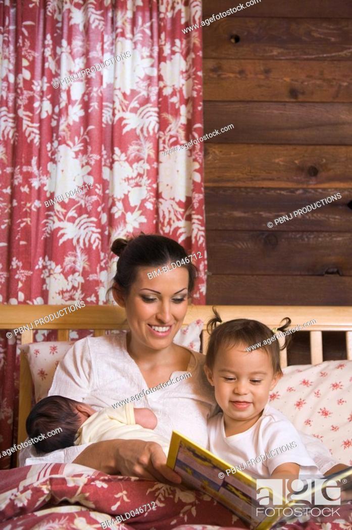 Stock Photo: Hispanic mother reading to daughter.