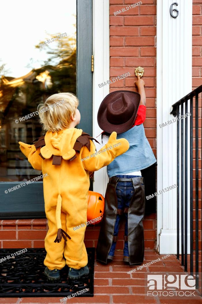 Stock Photo: Boys in costumes trick or treating together on Halloween.