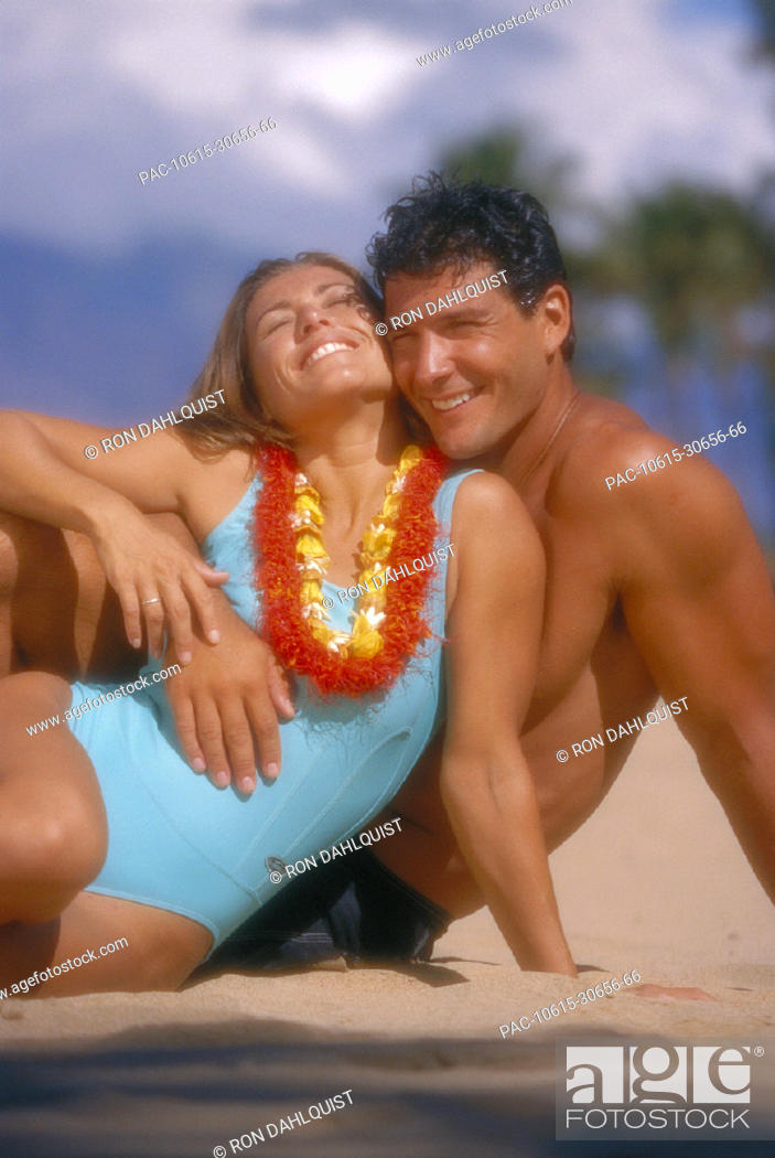 Stock Photo: Soft focus couple embrace on beach, woman wearing lei D1099.