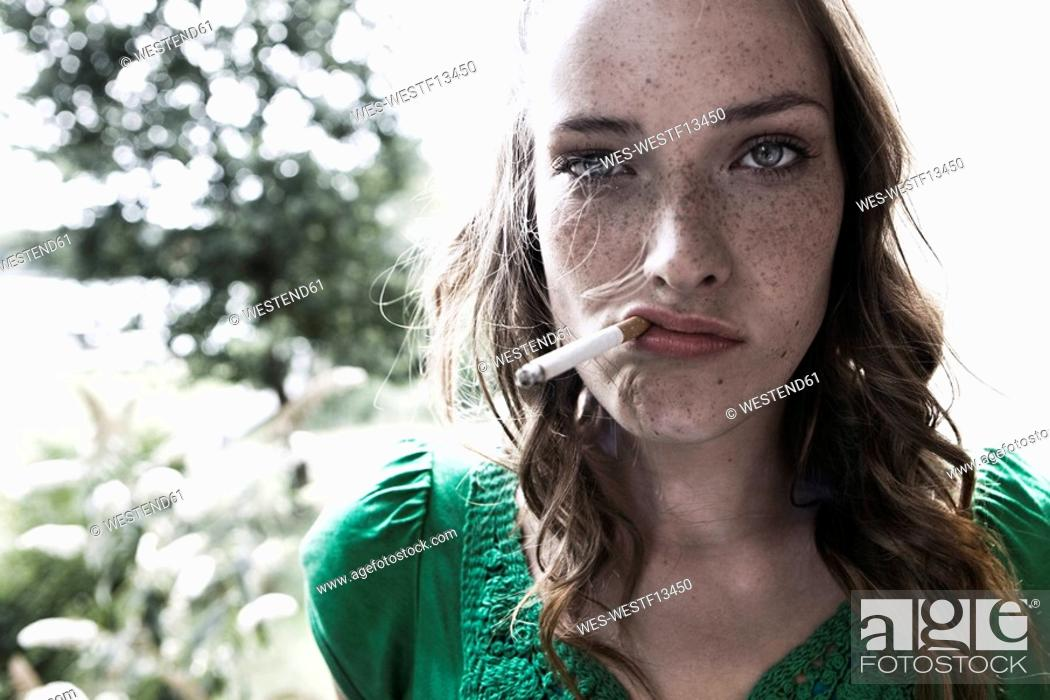 Stock Photo: Germany, Berlin, Young woman smoking cigarette, portrait, close-up.