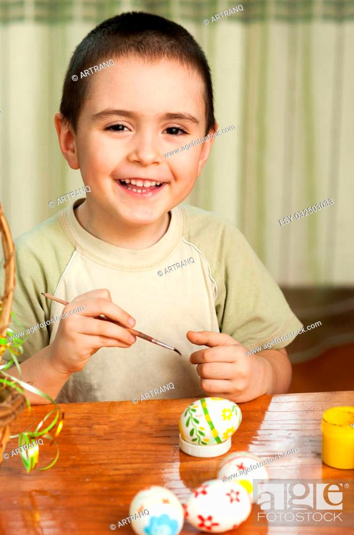 Stock Photo: funny boy colored Easter eggs sitting at the table.