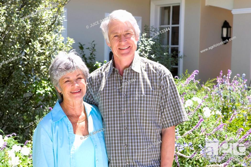 Stock Photo: Mature couple arm in arm outside house, smiling, portrait.