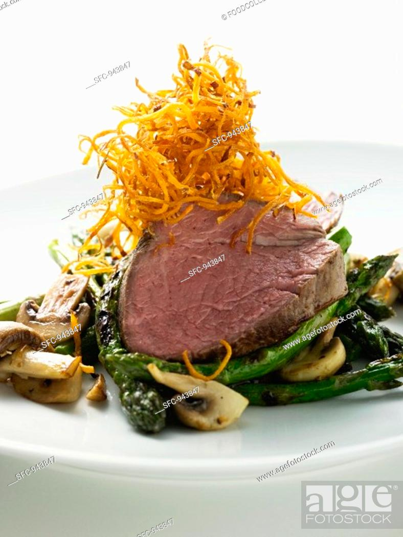 Stock Photo: Beef fillet on green asparagus.